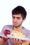 Young man food temptation. Man thinking what to eat between an apple and a cake (isolated on white Royalty Free Stock Images