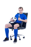 Young man in football form sitting with ball Stock Images
