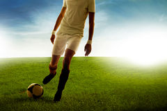 Young man football player score goals on the grass field Stock Photos