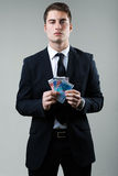Young man in formalwear holding money. Stock Image