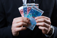 Young man in formalwear holding money. Stock Photo