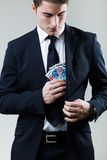Young man in formalwear putting money in his pocket. Royalty Free Stock Photos