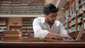 Young Man Found Information. Intellectual young man succeeded in finding information, good-looking boy in neat white shirt reading an old book, using laptop to stock video footage
