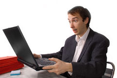 Young man freaks out in front of laptop Royalty Free Stock Photos