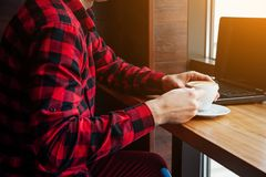 Young man freelancer enjoys coffee in cafe using laptop. Self-employed worker drinking coffee and waiting for a client. Young man freelancer enjoys coffee in Royalty Free Stock Photos