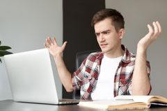 The young man freelancer programmer PC user with a disgruntled b. Itter angry expression on his face looking at the laptop in front of him by moving his hands Stock Photos