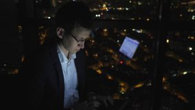 Young man freelancer is working on his computer near the window in home at night. Young man freelancer in glasses is working on his computer near the window in stock video