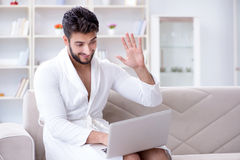 The young man freelancer working from home on a laptop. Young man freelancer working from home on a laptop Stock Photos
