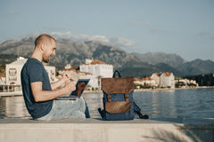 Young man freelancer working with laptop and Achieved success si. Tting near sea Stock Image