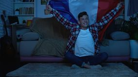 Young man with French flag cheering favorite football team home, sports event. Stock footage stock video