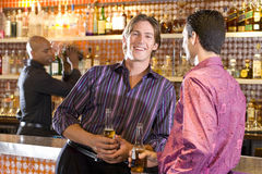 Young man and friend at bar with drinks, smiling, portrait Royalty Free Stock Photo