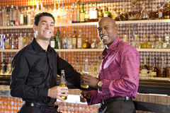 Young man and friend at bar with drinks, smiling, portrait Stock Photography