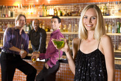 Young man and friend at bar looking at woman with cocktail, smiling, portrait. Young men and friend at bar looking at women with cocktail, smiling, portrait stock photography