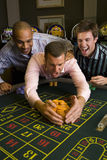 Young man with friends collecting pile of gambling chips from roulette table in casino, smiling. Young men with friends collecting pile of gambling chips from stock photography