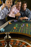 Young man and friends gambling at roulette table in casino, smiling Royalty Free Stock Image