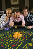 Young man with friends gambling at roulette table in casino, smiling Stock Photo