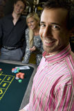 Young man by friends gambling at roulette table, smiling, portrait, close-up Royalty Free Stock Photography
