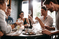 Young man with friends at restaurant. Young men raising his glass of wine with friends at restaurant. Young people enjoying dinner at a cafe Stock Photography