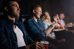 Young man with friends watching movie in cinema. Young men with friends watching movie in cinema. Group of people in theater with popcorn and drinks royalty free stock image