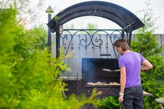 Young man fries steaks on the grill outdoor in his yard Royalty Free Stock Photography