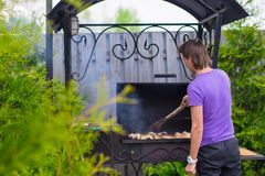 Young man fries steaks on the grill outdoor in his yard Royalty Free Stock Images