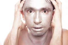 Young man with frightened eyes and bronzed makeup Royalty Free Stock Images