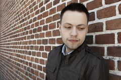 Young man in fron of the brick wall Royalty Free Stock Photography