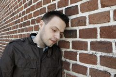 Young man in front of the brick wall Royalty Free Stock Image