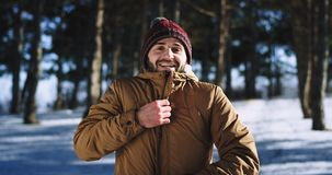 Young man in front of the camera very charismatic enjoying the time at nature on the snowy forest amp large feeling. Happy stock video