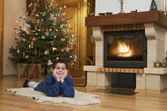 Young man front of fireplace at Christmas Stock Image