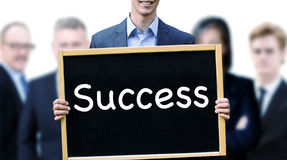 Young man in front of group holding sign with word Success stock photography