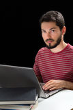 Young man in front of laptop hands over keyboard Stock Image