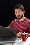 Young man in front of laptop hands over keyboard Stock Images