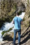 Young Man in front of a Lush Waterfall Stock Photos