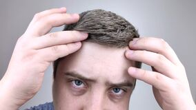 A young man in front of a mirror examines his early gray hair. The concept of early hair bleaching