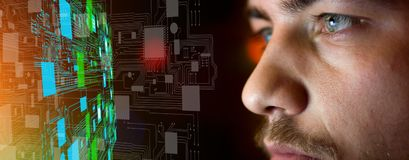 Young man in front of circuit board architecture - technology co stock photography