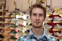 Young man in front of running shoes. A young, blonde guy standing in front of a lot of running shoes Stock Image