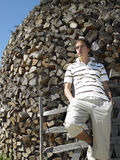 Young Man in Front of Woodpile. Young man leaning against pile of cut wood. Vertical shot Royalty Free Stock Photo