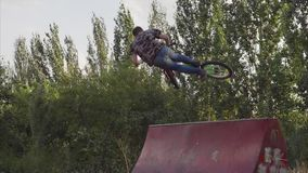 The young man fulfills tricks on a BMX bike. stock footage