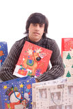 Young man full of Christmas gifts Royalty Free Stock Image