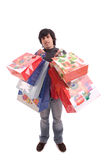 Young man full of Christmas gifts Royalty Free Stock Images