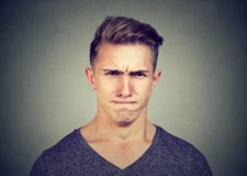 Young man full of hatred looking pissed off and annoyed. Squinting eyes and frowning Royalty Free Stock Images