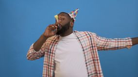 Young man in funny birthday party hat with playing pipe looking aside celebrating isolated on bright blue background. People sincere emotions lifestyle concept stock video footage