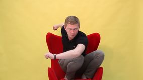 The young man is funny dancing on the armchair on a yellow background stock video footage