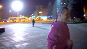 Young man funny dancing in the street at night. Slow motion. hipster man dancing outside. professional dancer male on stock video footage