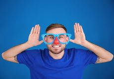 Young man in funny disguise posing. On color background. April fool`s day celebration Royalty Free Stock Photos