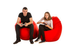 Young man and funny girl playing video games while sitting on re Royalty Free Stock Image