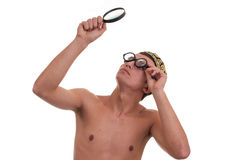 Young man with funny glasses looking through magnifyin Stock Photos