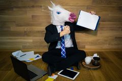 Young man in funny mask sits on the floor against a wall and shows a white empty sheet. With copy space. Any text possible .. Unicorn in a suit and tie smiles Royalty Free Stock Images