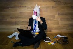 Young man in funny rubber mask sits on the floor. Against a wall and works at home office. Unicorn in a suit and tie drinks coffee with a lot of gadgets around Stock Photography